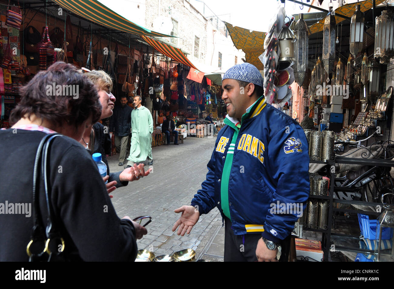 A street salesman tries to sell to tourists in the Medina, Marrakesh - Stock Image