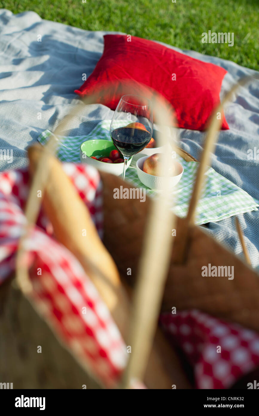 Food and drink on picnic blanket - Stock Image