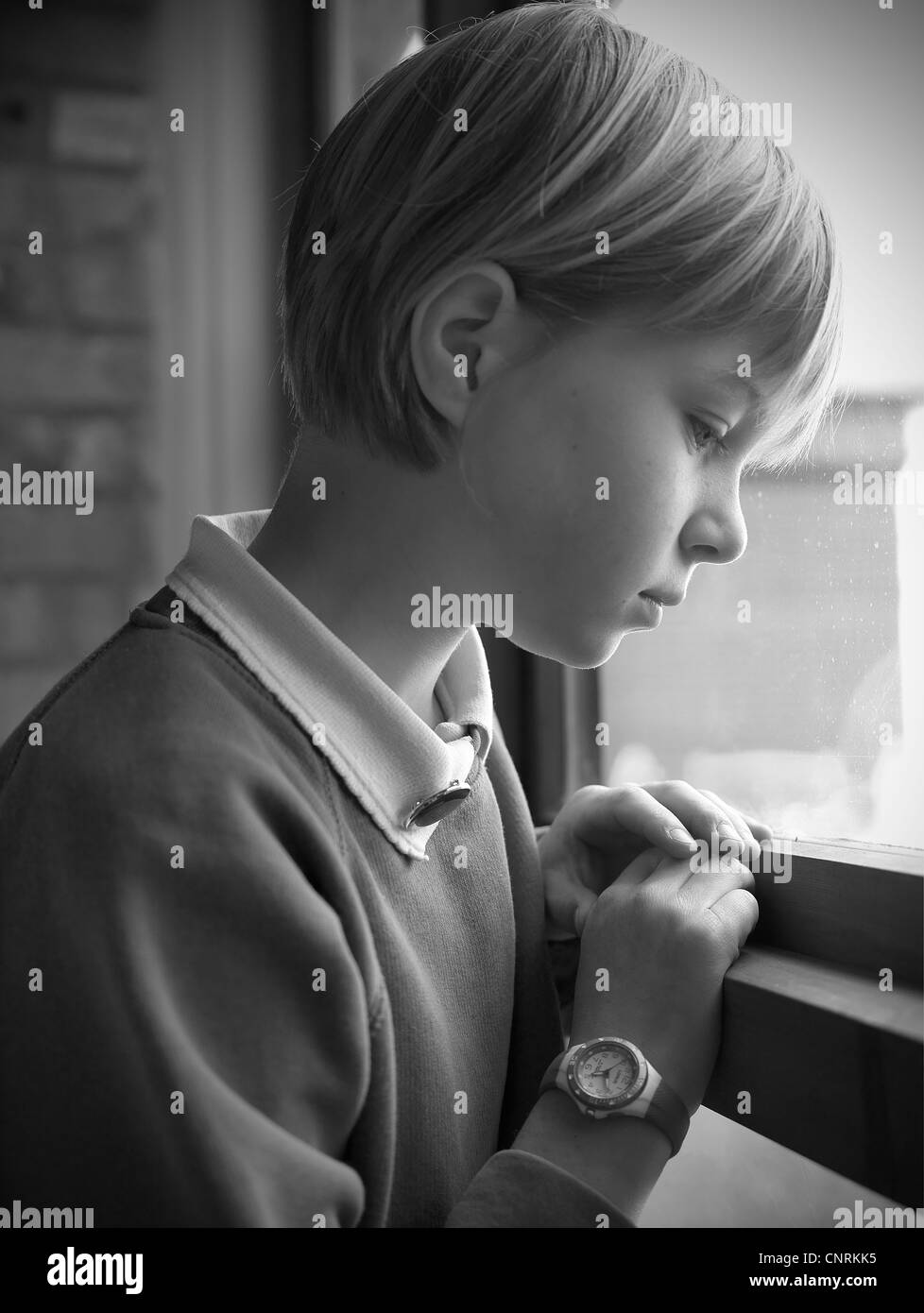 School girl looking out of window stock image