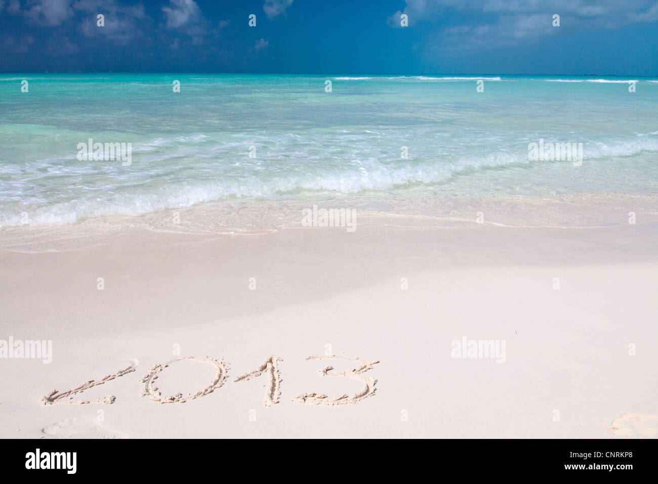 Year 2013 hand written on the white sand in front of the sea - Stock Image