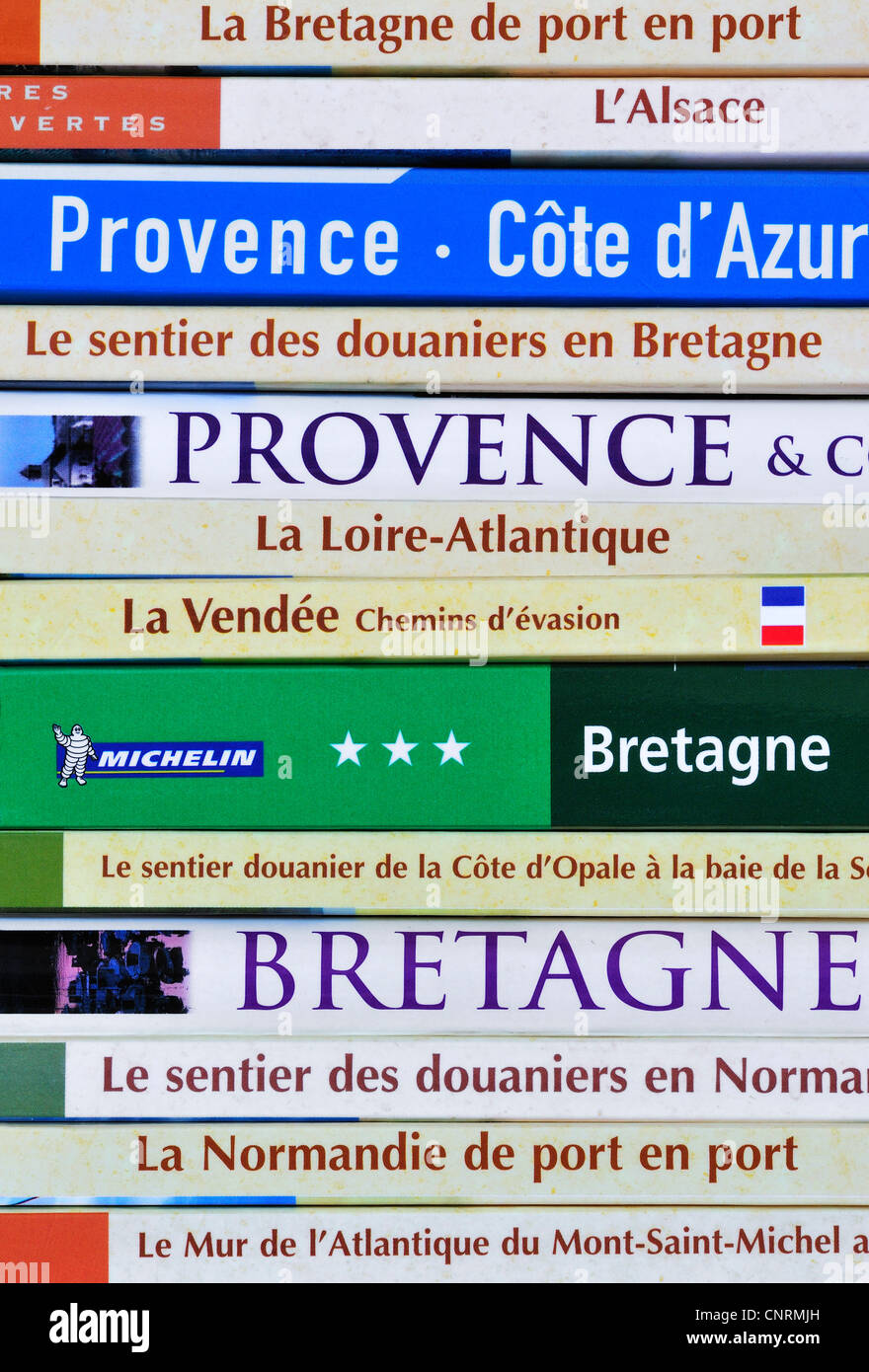 French collection of travel guides and assortment of guidebooks about France on bookcase bookshelf - Stock Image