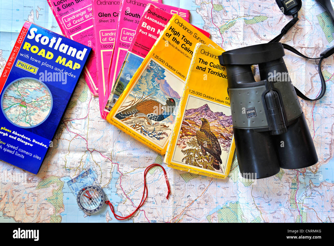 Compass, binoculars and assortment of Scottish Ordnance Survey topographical maps about Scotland, UK to plan wildlife - Stock Image