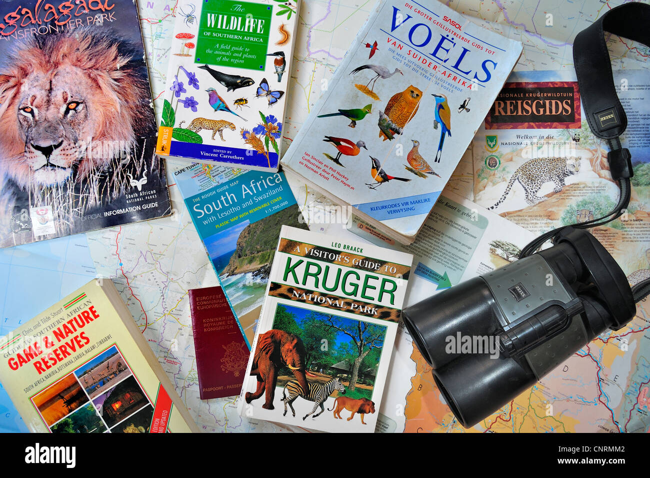 Binoculars, travel guides, guidebooks, African wildlife determination books and South African map for planning safari - Stock Image