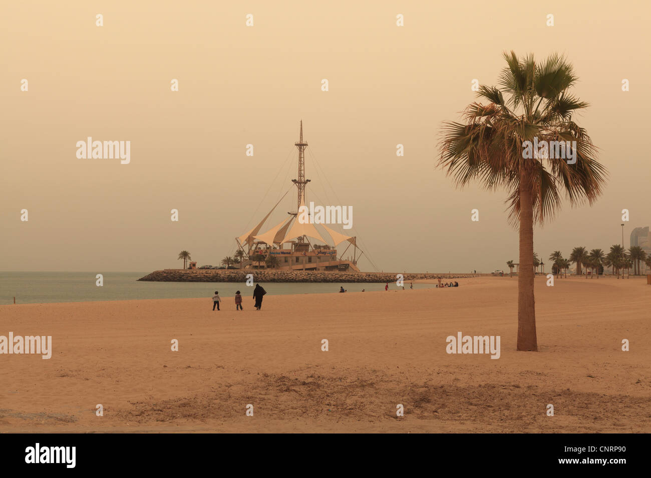 A beach in Kuwait City with the Marina Waves building in the background - Stock Image
