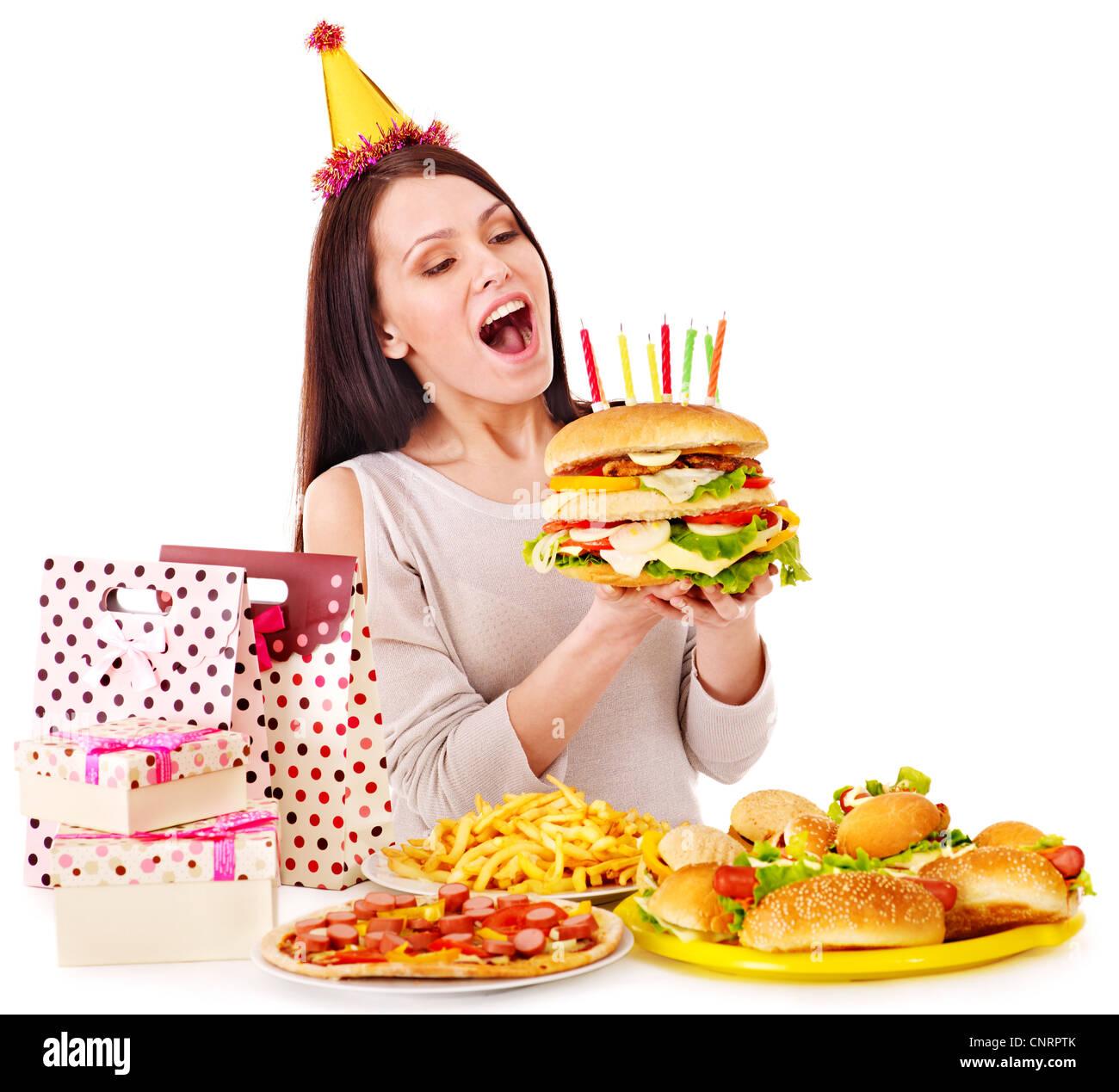 Woman eating hamburger at birthday. Isolated. - Stock Image