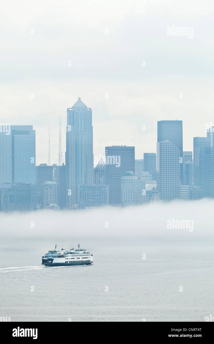 A Washington State Ferry approaching Seattle with a fog bank over downtown Seattle, USA - Stock Image