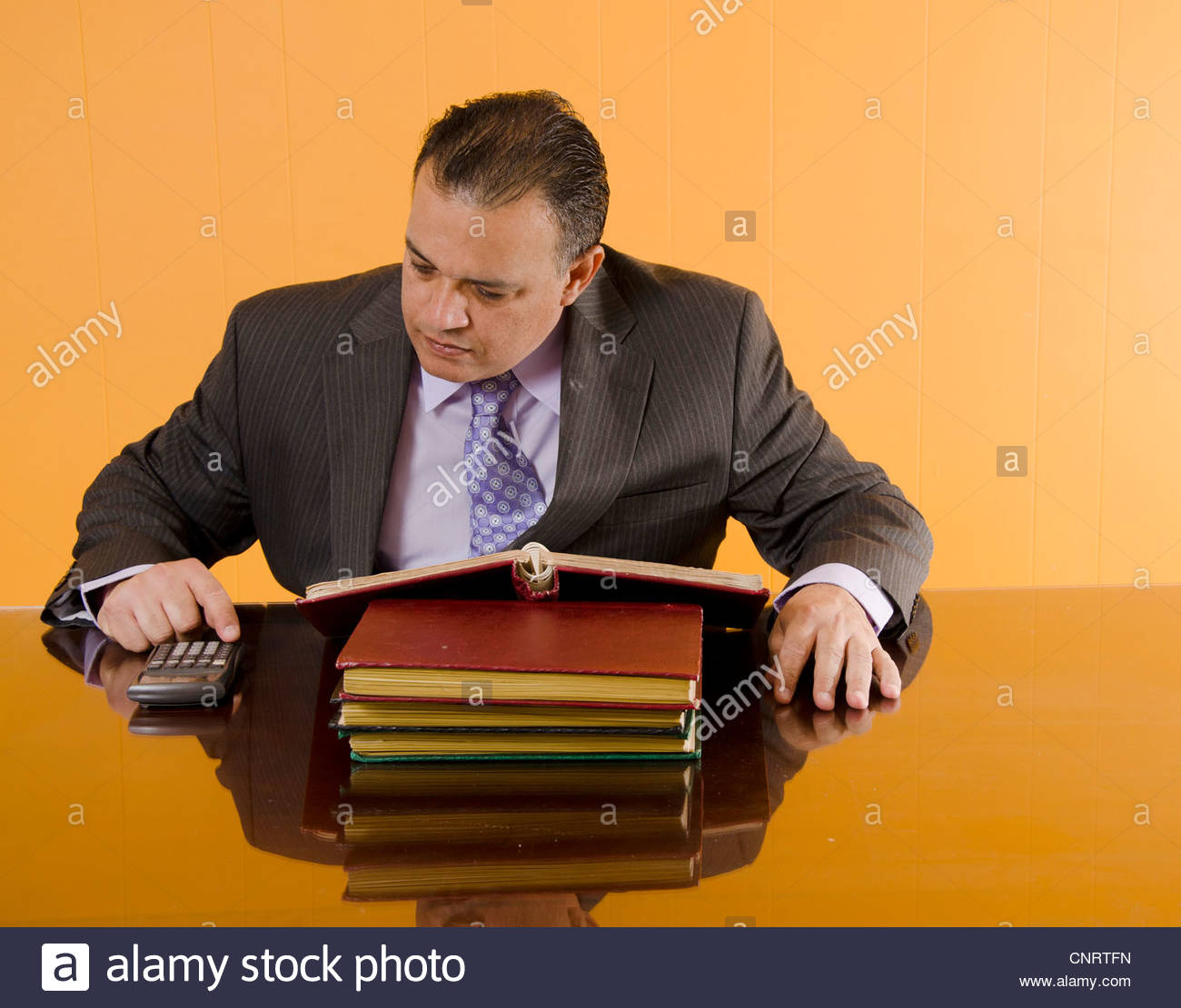 Bookkeeper in his office doing math - Stock Image