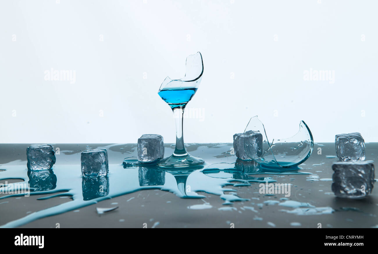 Wineglass broken by fallen icecubes Stock Photo