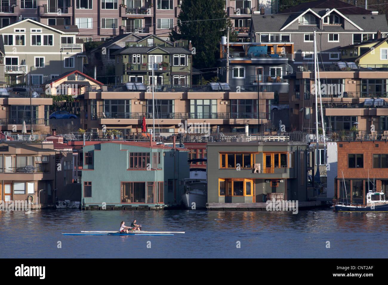 Sculling passed houseboats on Lake Union, Seattle, Washington - Stock Image
