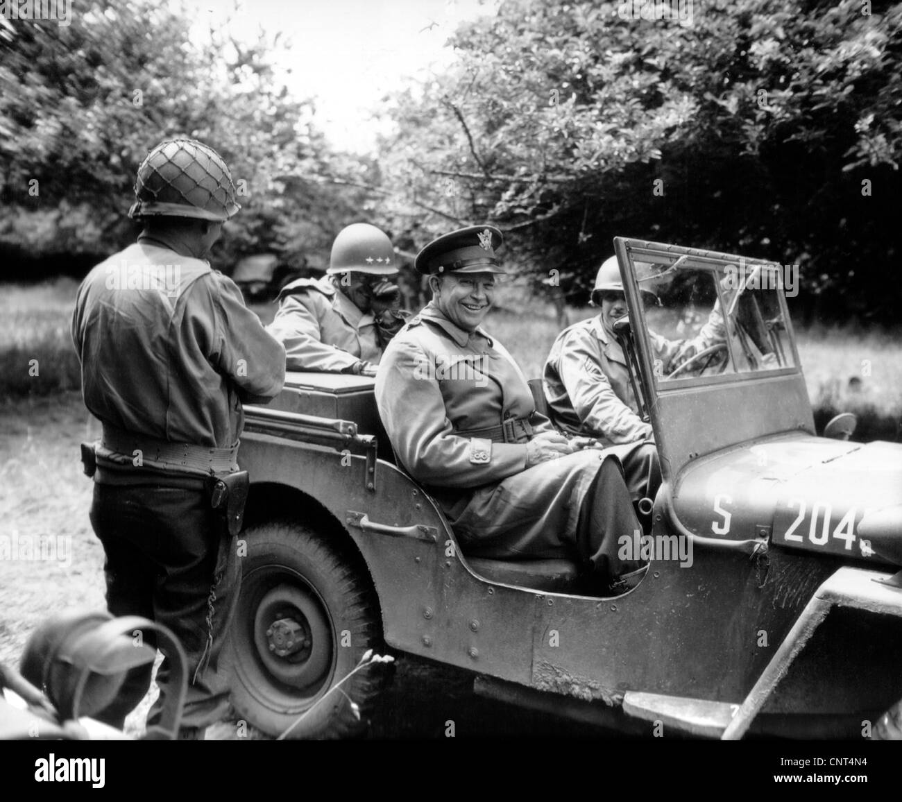 Vintage World War II photo of General Dwight D. Eisenhower sitting in a jeep talking with other officers. - Stock Image