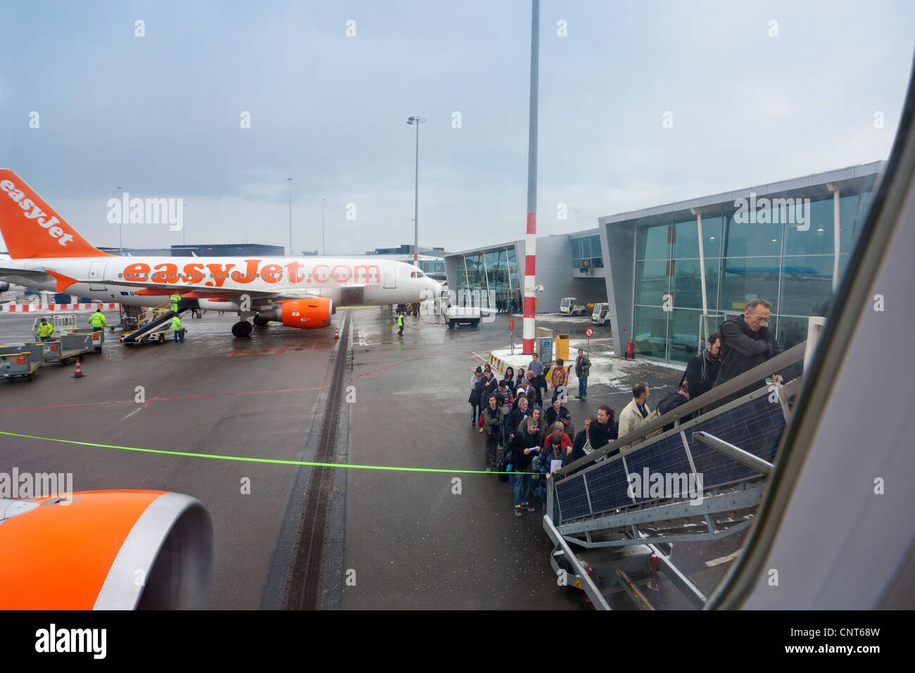 Amsterdam Schiphol Airport People boarding EasyJet plane airplane aeroplane mobile staircase stairs in winter. H - Stock Image