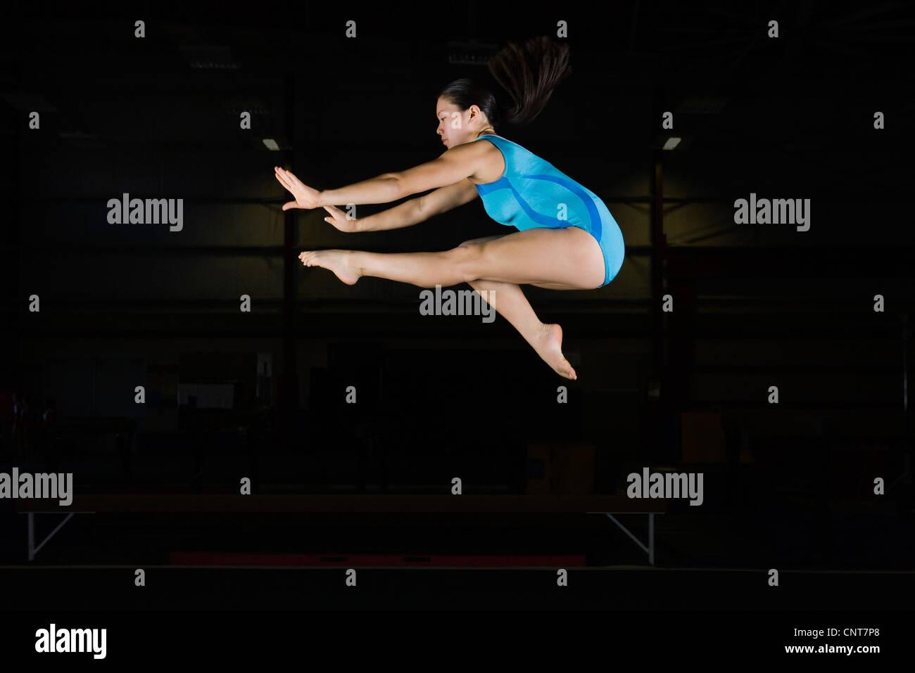 Teenage girl gymnast jumping on balance beam - Stock Image