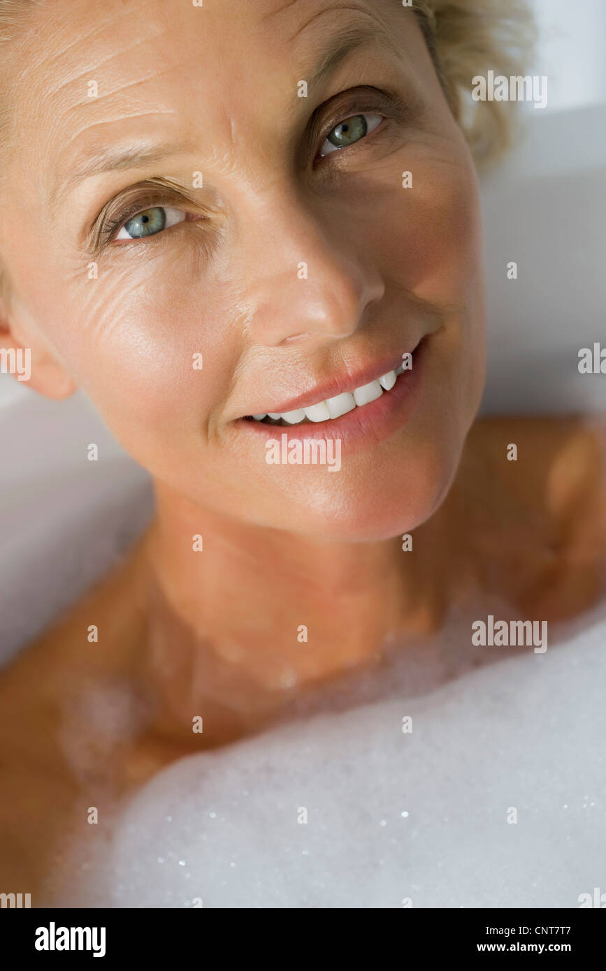 Mature woman relaxing in bubble bath, cropped - Stock Image