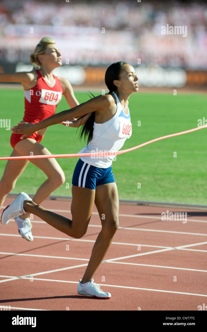 Female runner crossing finish line - Stock Image