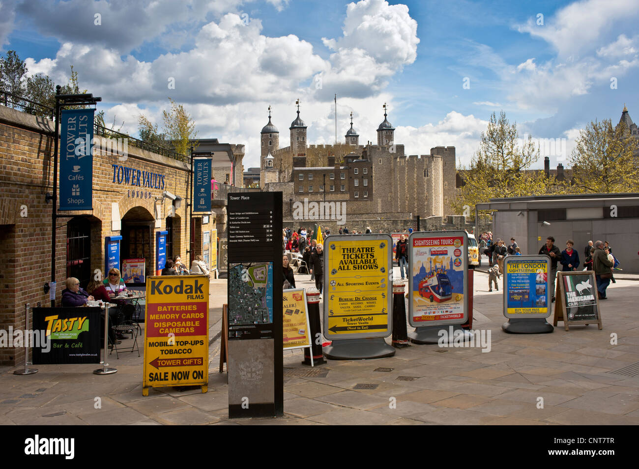 Advertising Signs on the open space at Tower Place close to Tower of London with the Tower in the background - Stock Image