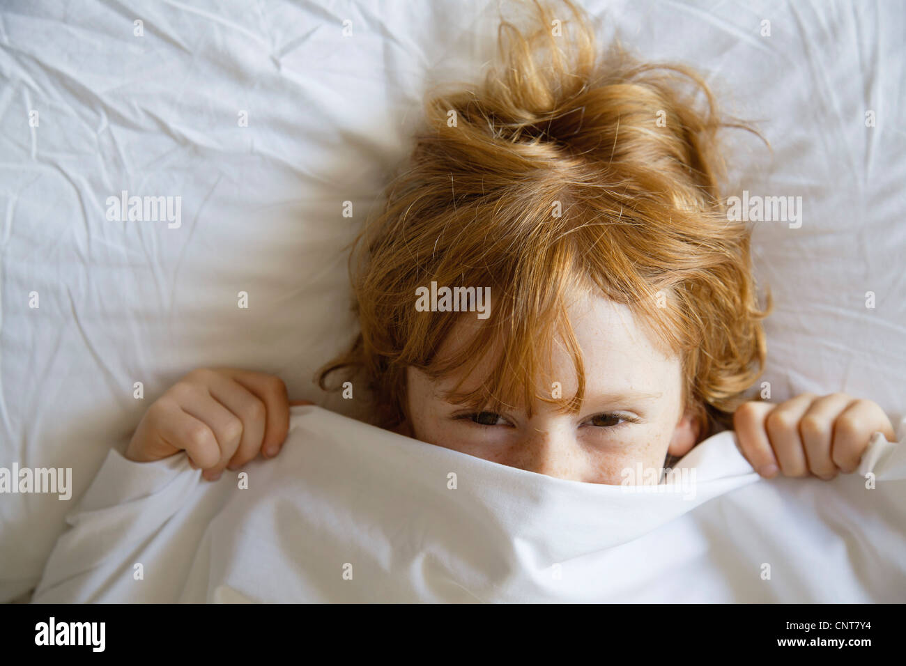 Boy covering face with bed sheet, directly above - Stock Image