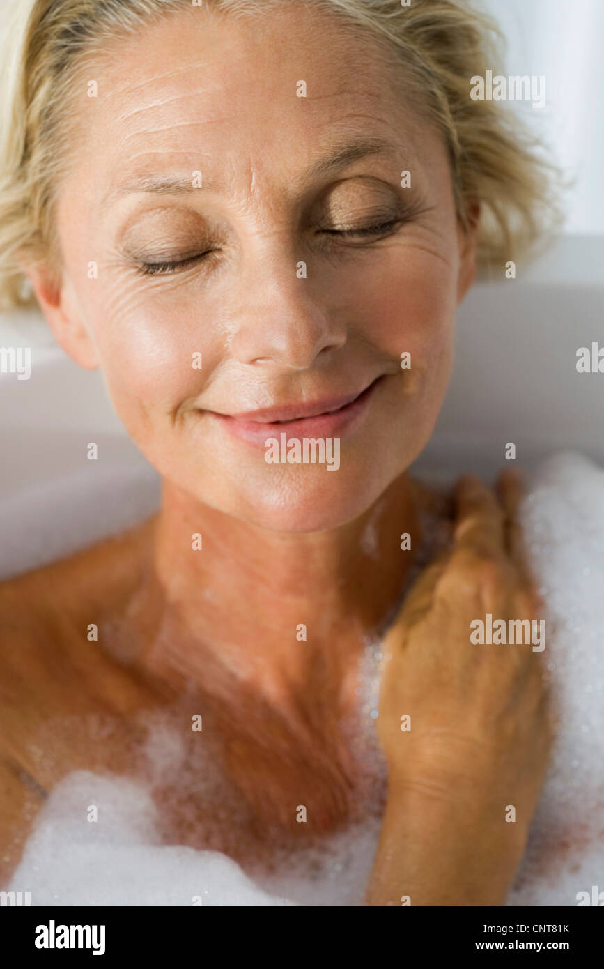 Mature woman relaxing in bubble bath with eyes closed, portrait - Stock Image