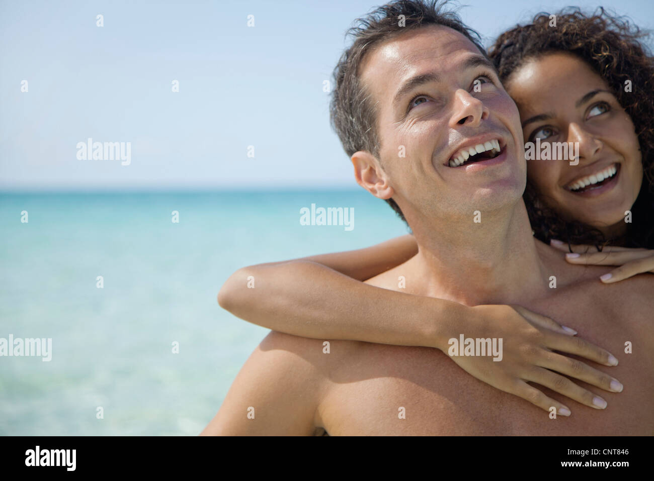 Couple together at the beach, looking up and smiling - Stock Image
