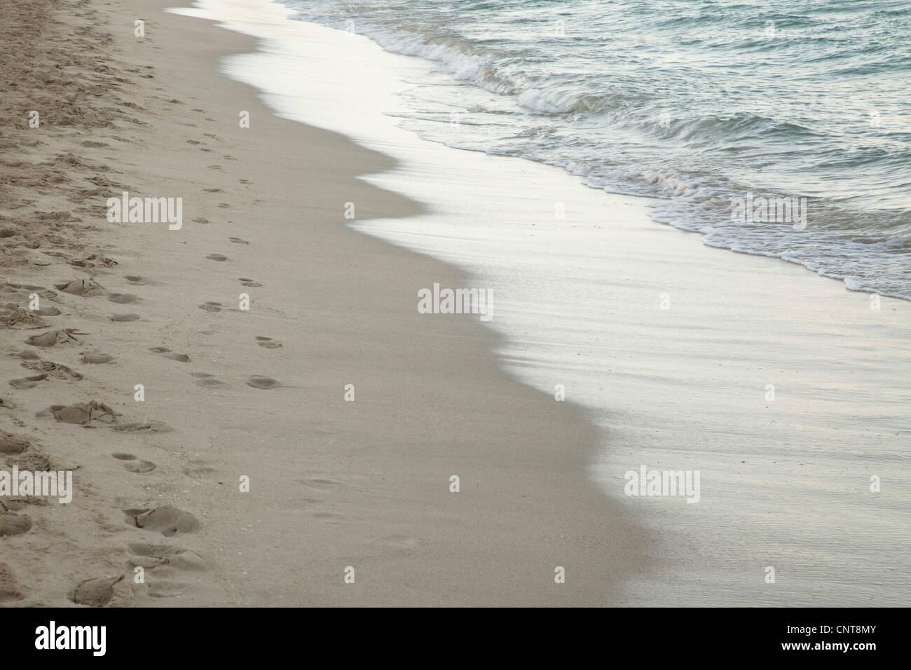 Wave washing onto shore - Stock Image