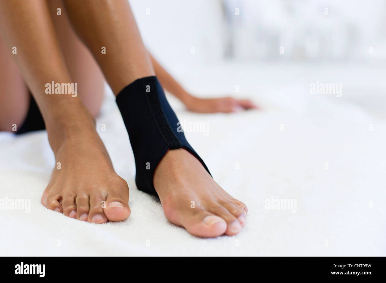Woman wearing ankle brace, low section - Stock Image