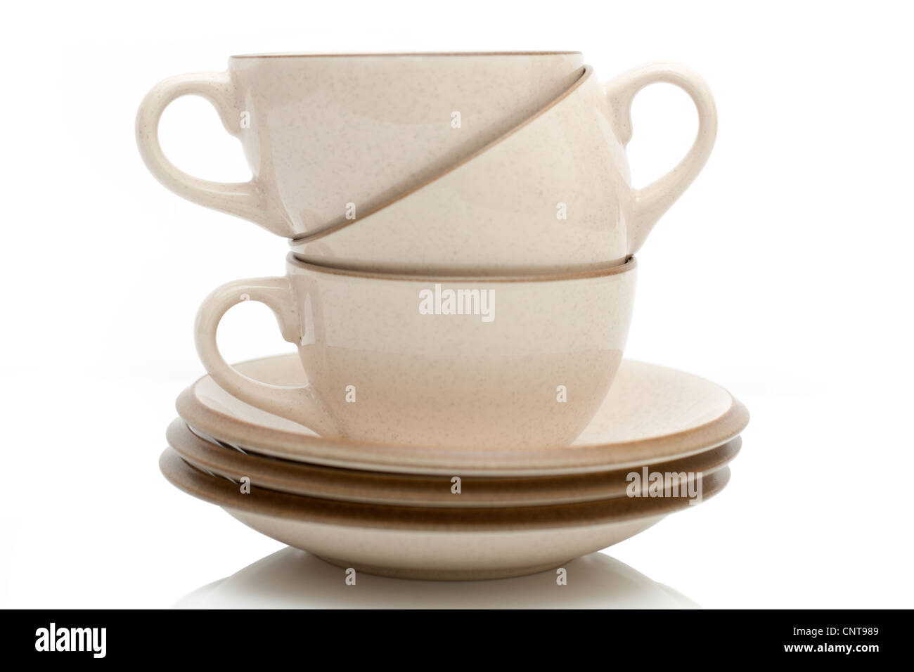 Three stacked beige coffee cups and saucers - Stock Image