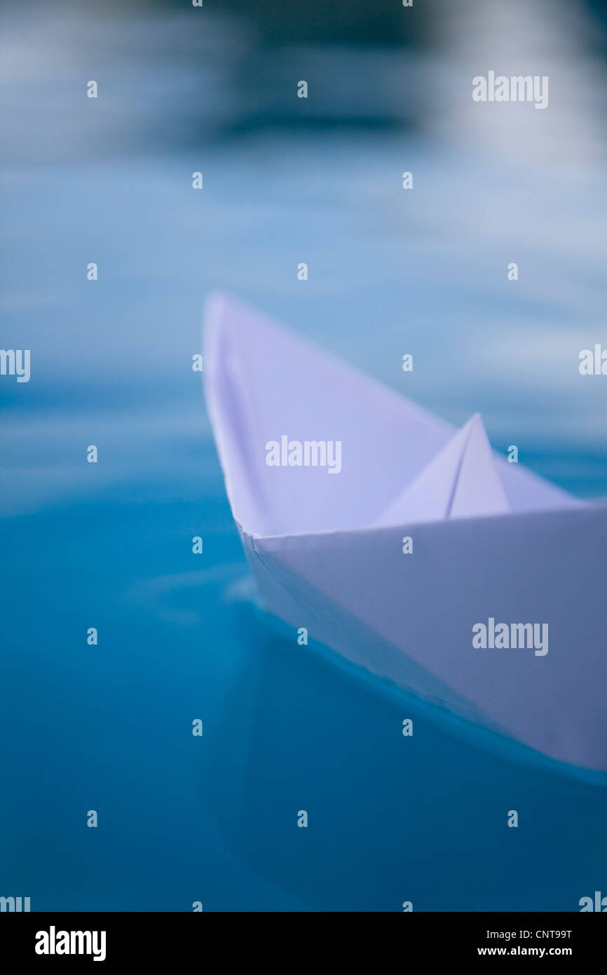 Paper boat floating on water - Stock Image