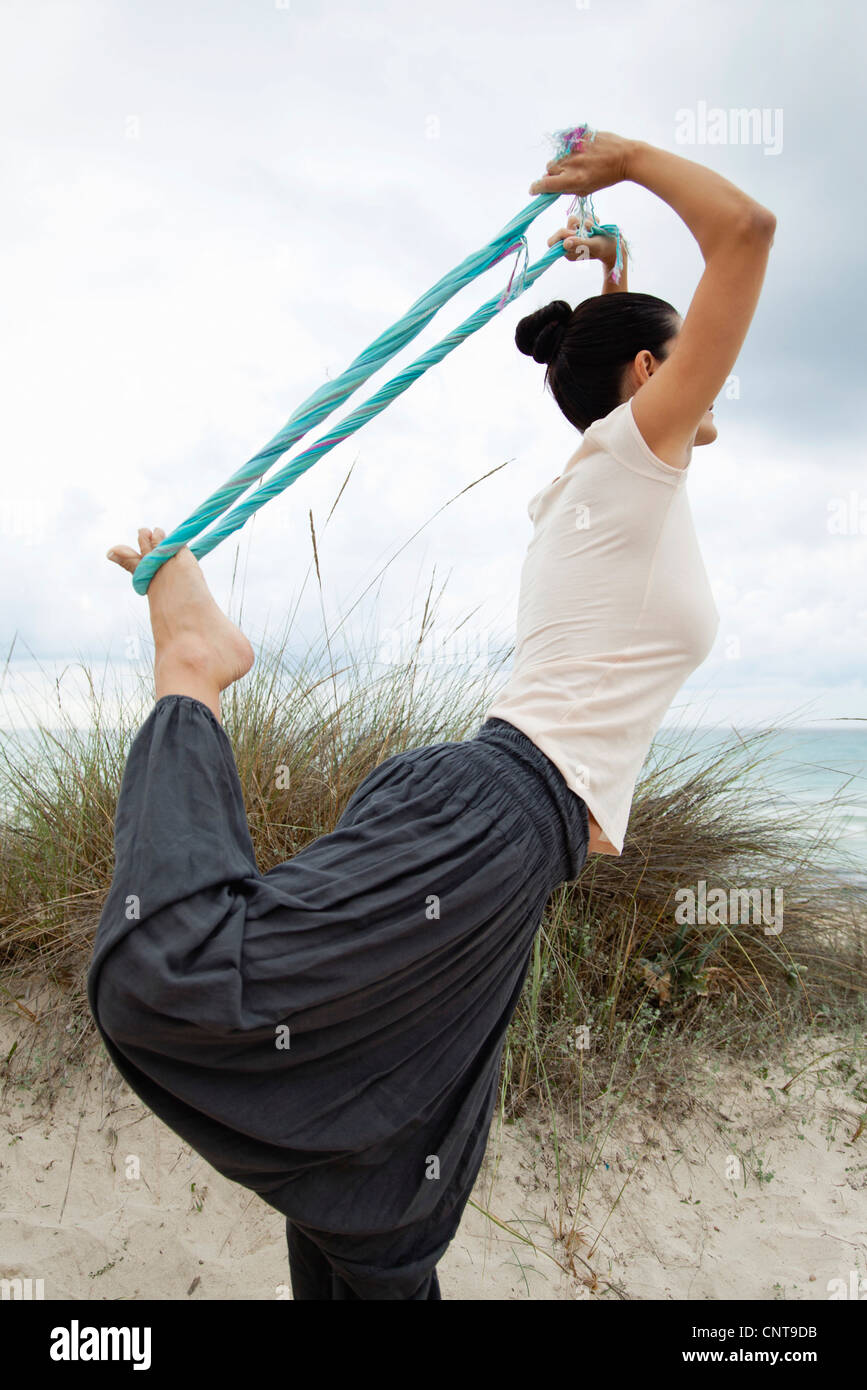 Woman in Natarajasana pose on beach, side view - Stock Image