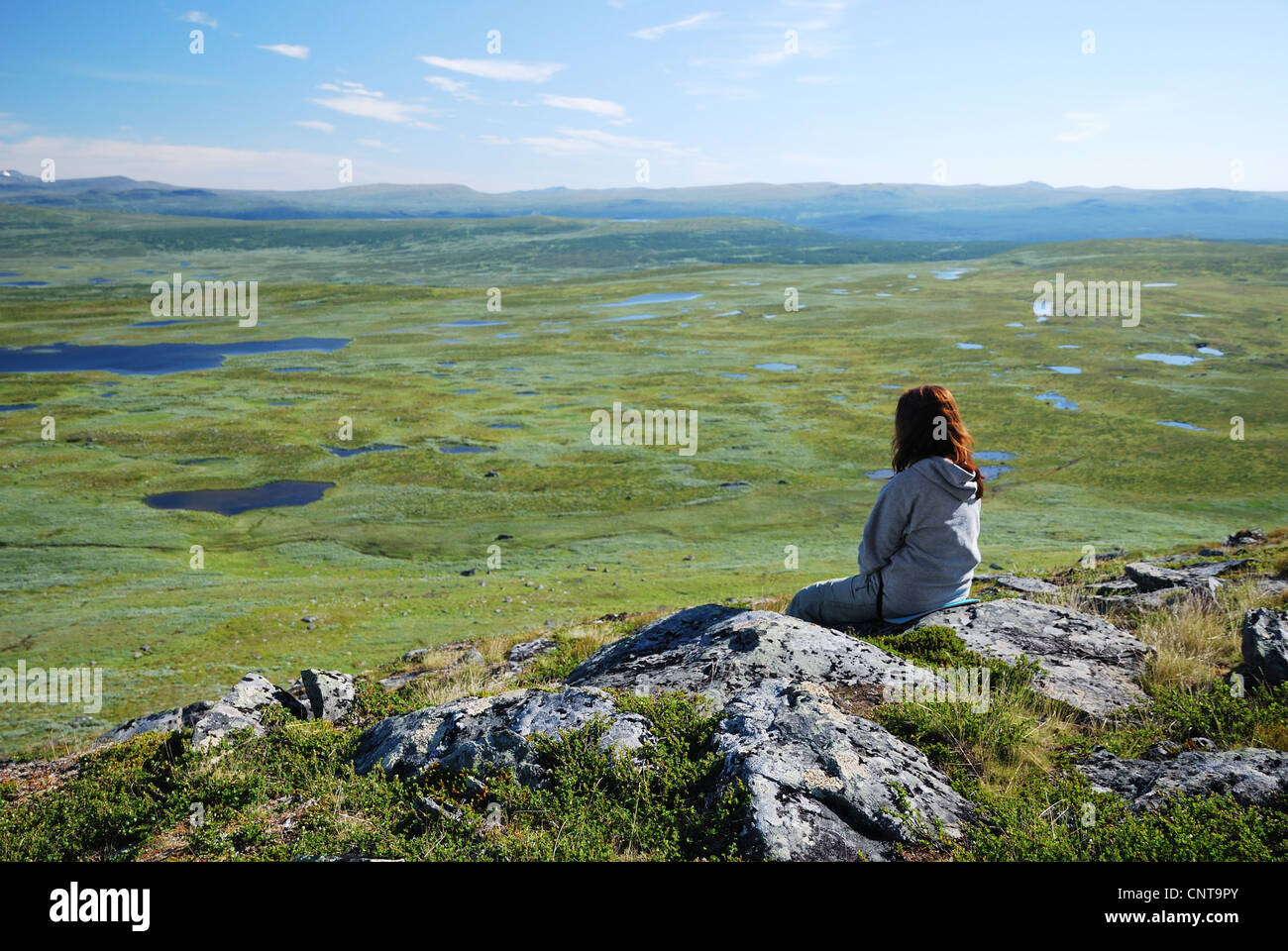 Woman against the green tableland with many small lakes. - Stock Image