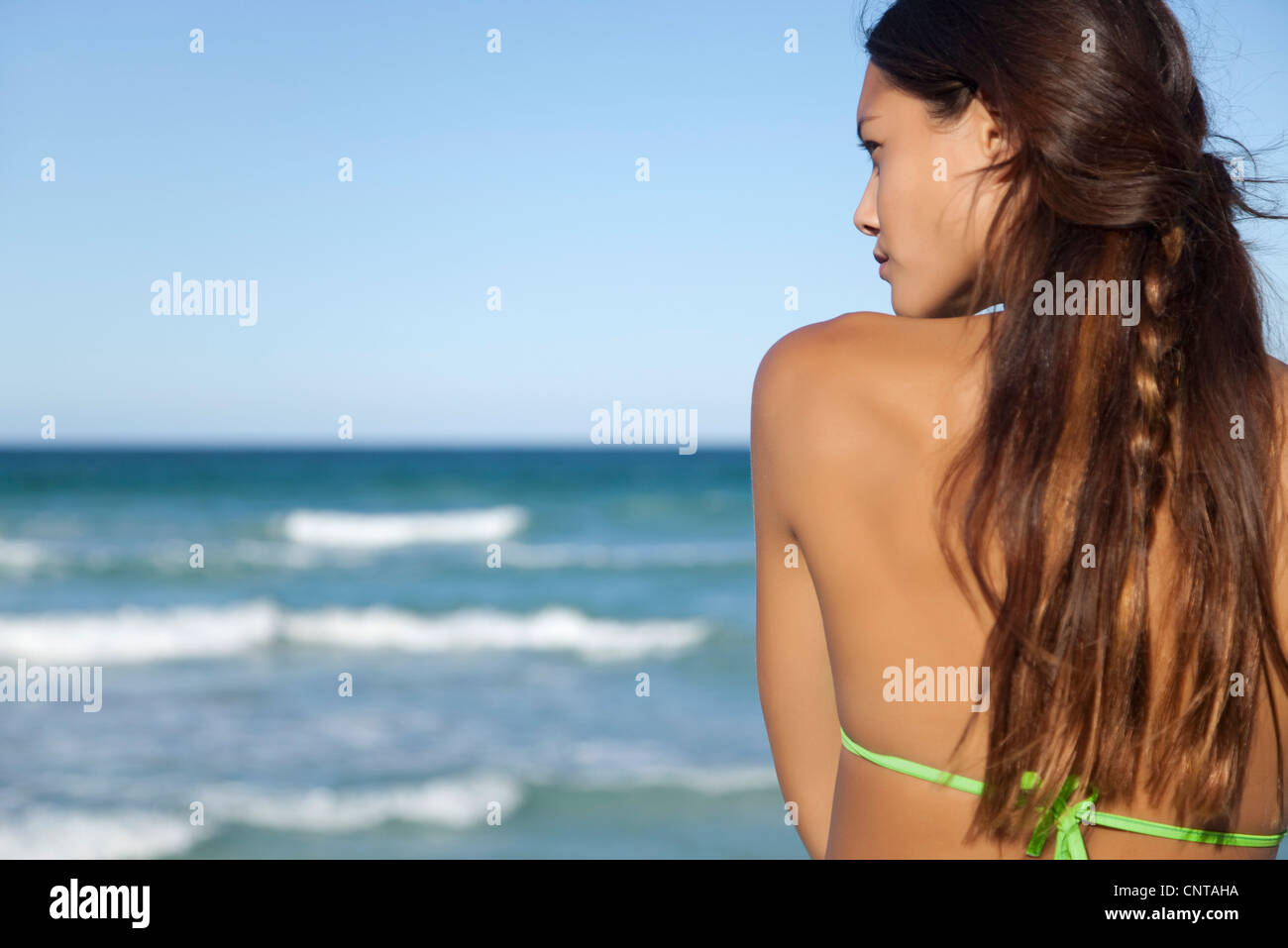 Young woman looking at ocean view, rear view - Stock Image
