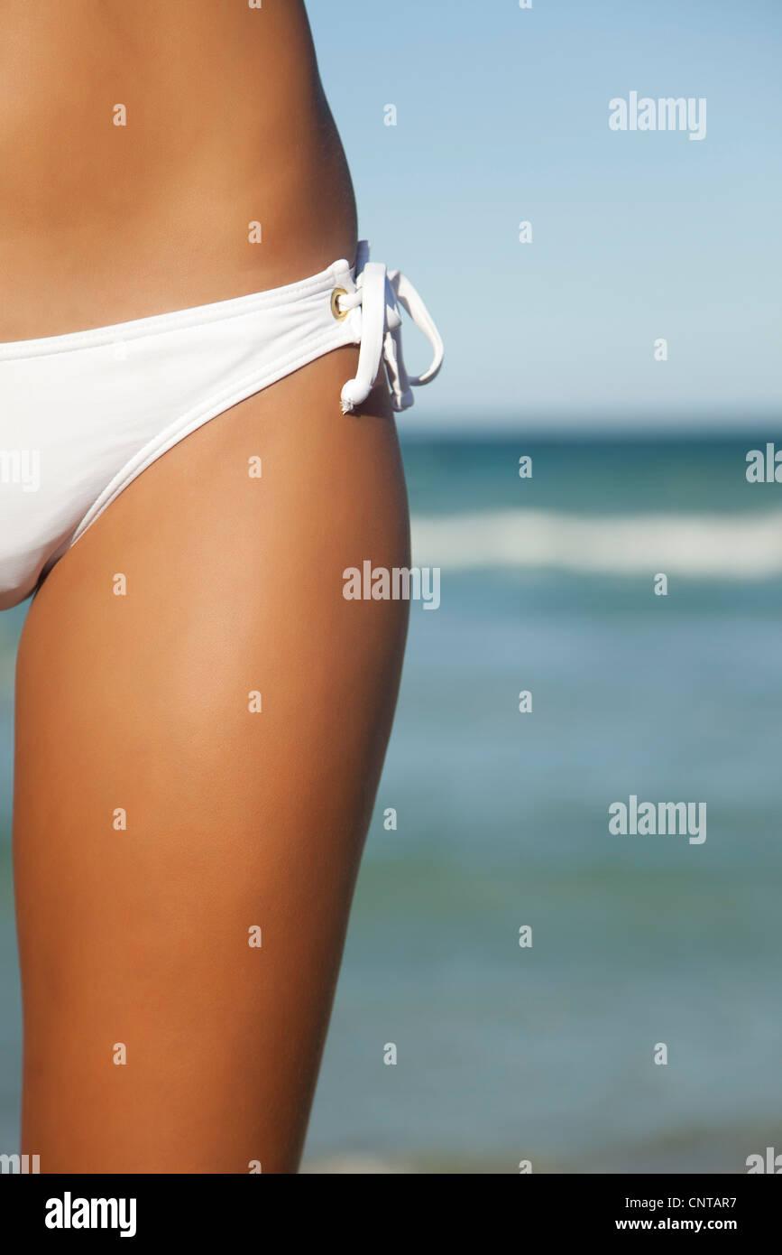 Woman in bikini bottom, mid section - Stock Image