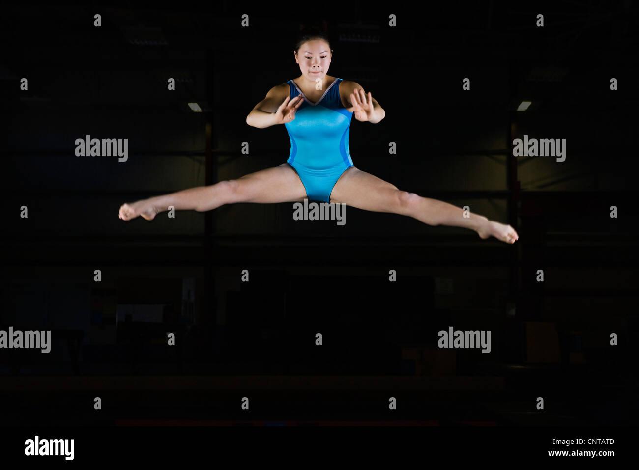 Teenage girl gymnast performing split leap - Stock Image