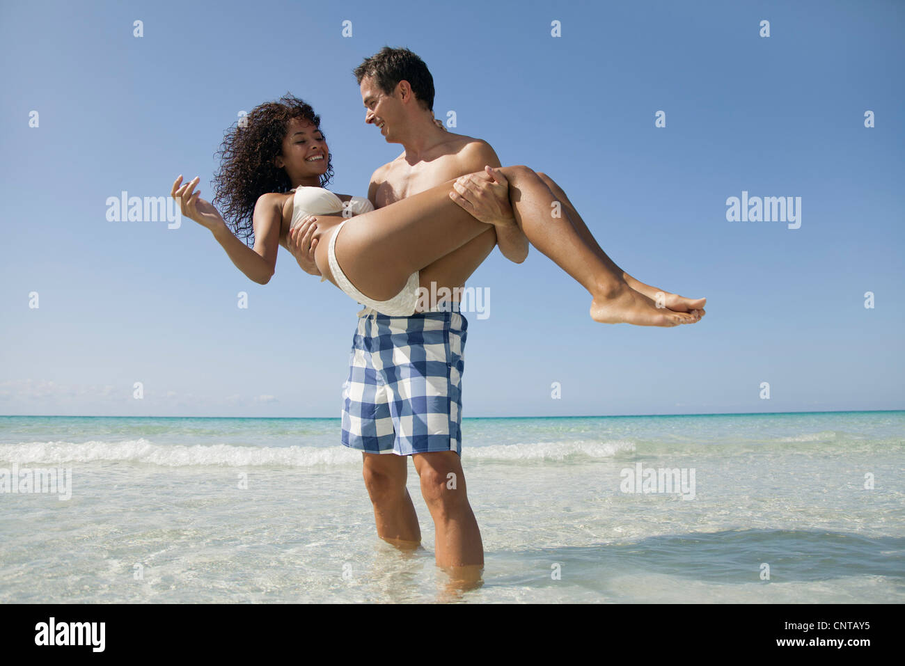 Couple together at the beach, man carrying woman - Stock Image