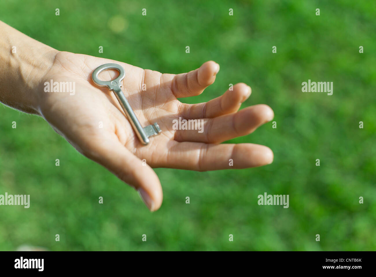 Woman holding key in palm - Stock Image