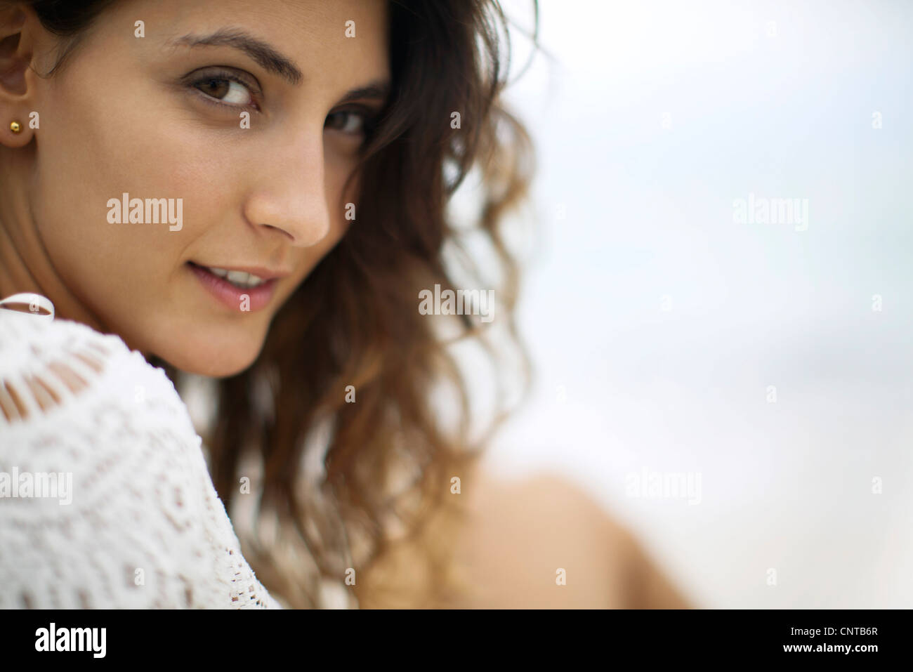 Young woman looking over shoulder, cropped - Stock Image
