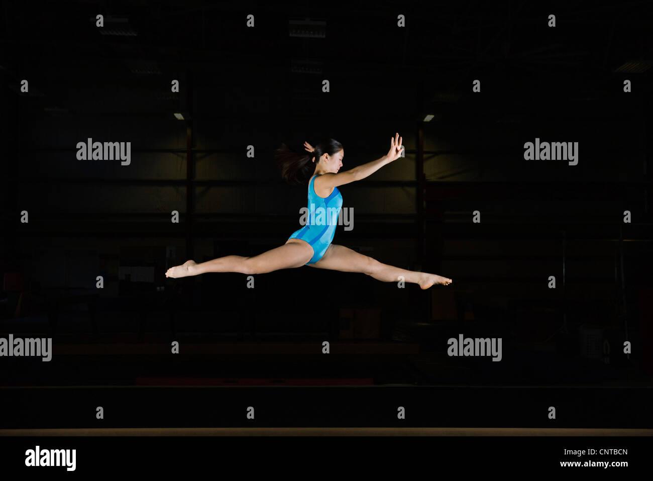 Tenage girl gymnast performing split leap - Stock Image
