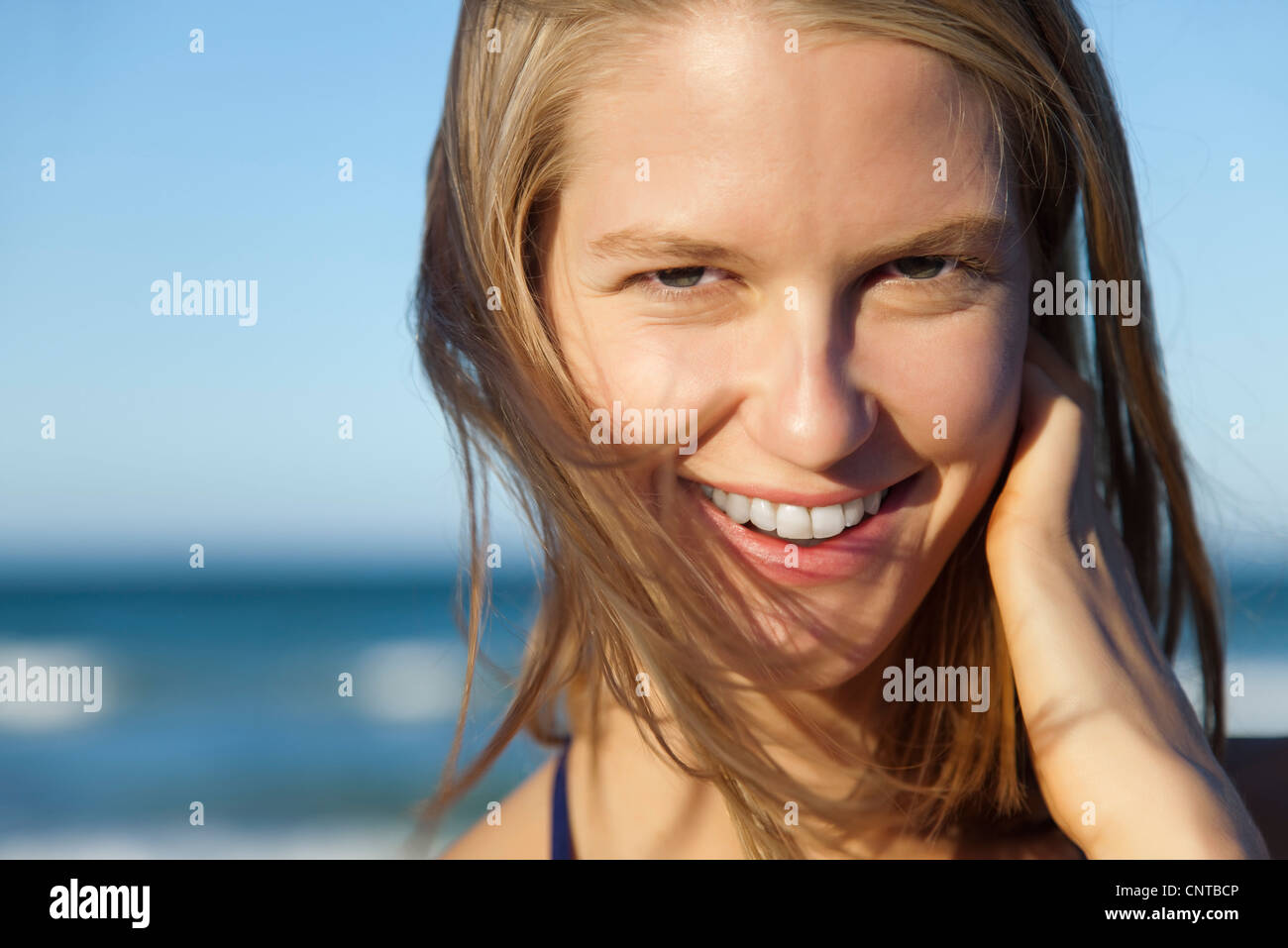 Smiling young woman with tousled hair, portrait - Stock Image