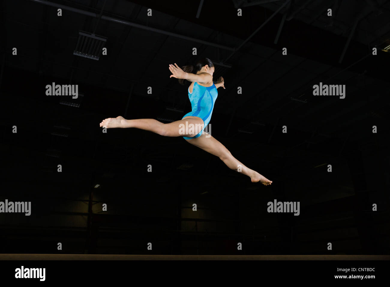 Teenage girl gymnast performing split leap, low angle view - Stock Image