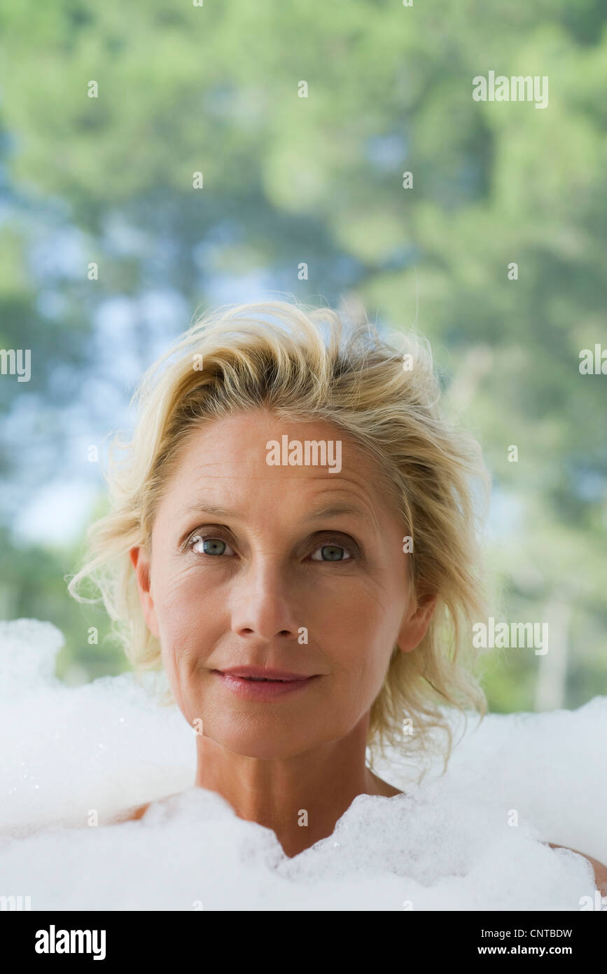 Mature woman in bubble bath, portrait - Stock Image