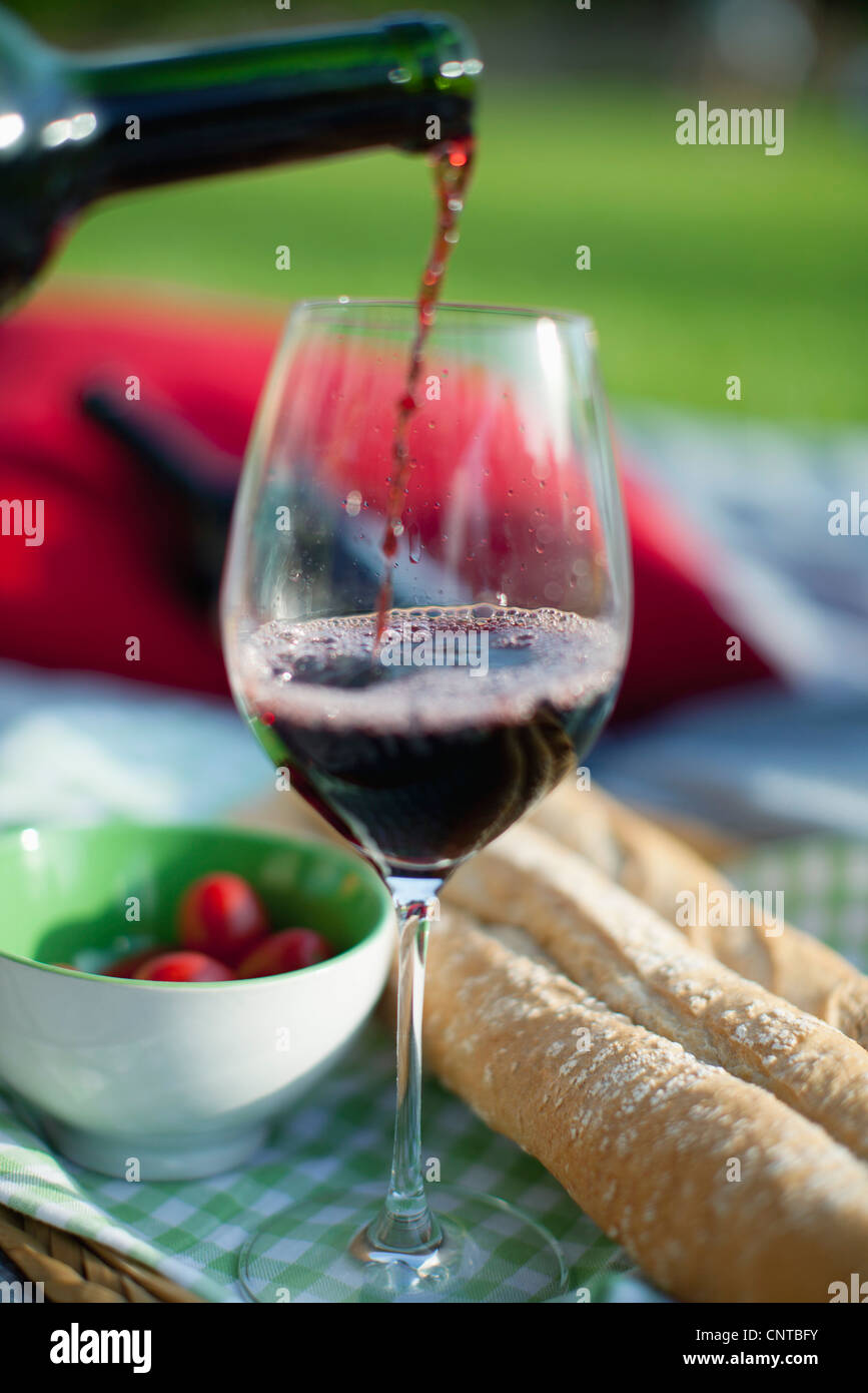 Pouring red wine at picnic - Stock Image