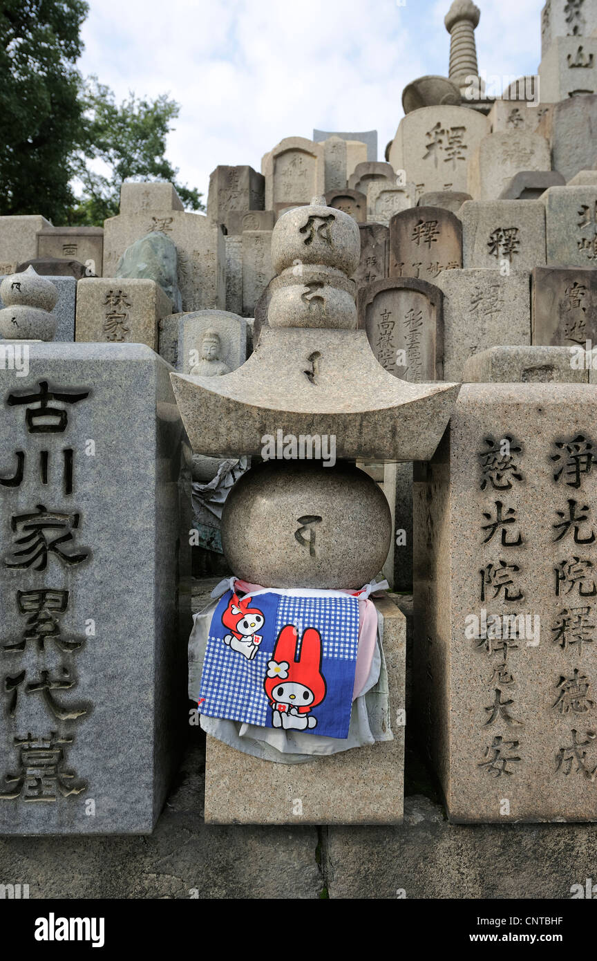 pile of grave marker stones decorated with bibs at Shitenno-Ji temple, Osaka, Japan - Stock Image