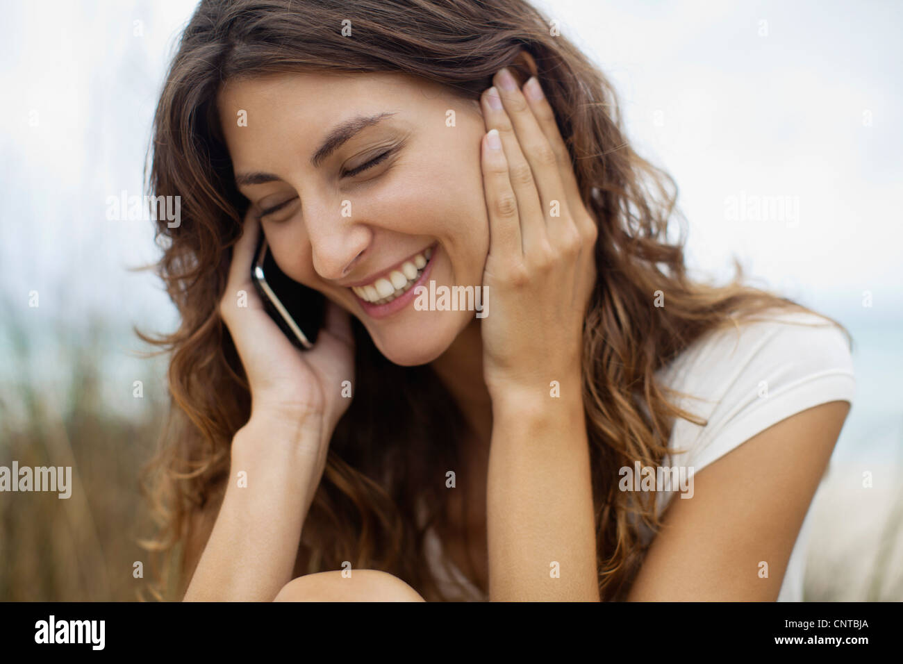Happy young woman talking on cell phone, portrait - Stock Image