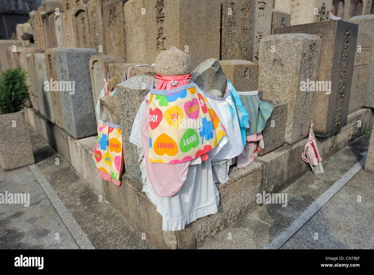 grave marker stones decorated with bibs at Shitenno-Ji temple, Osaka, Japan - Stock Image