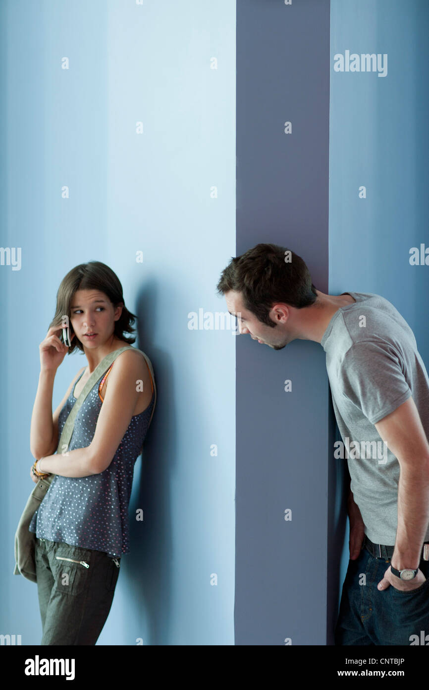 Young man interrupting young woman's cell phone call - Stock Image