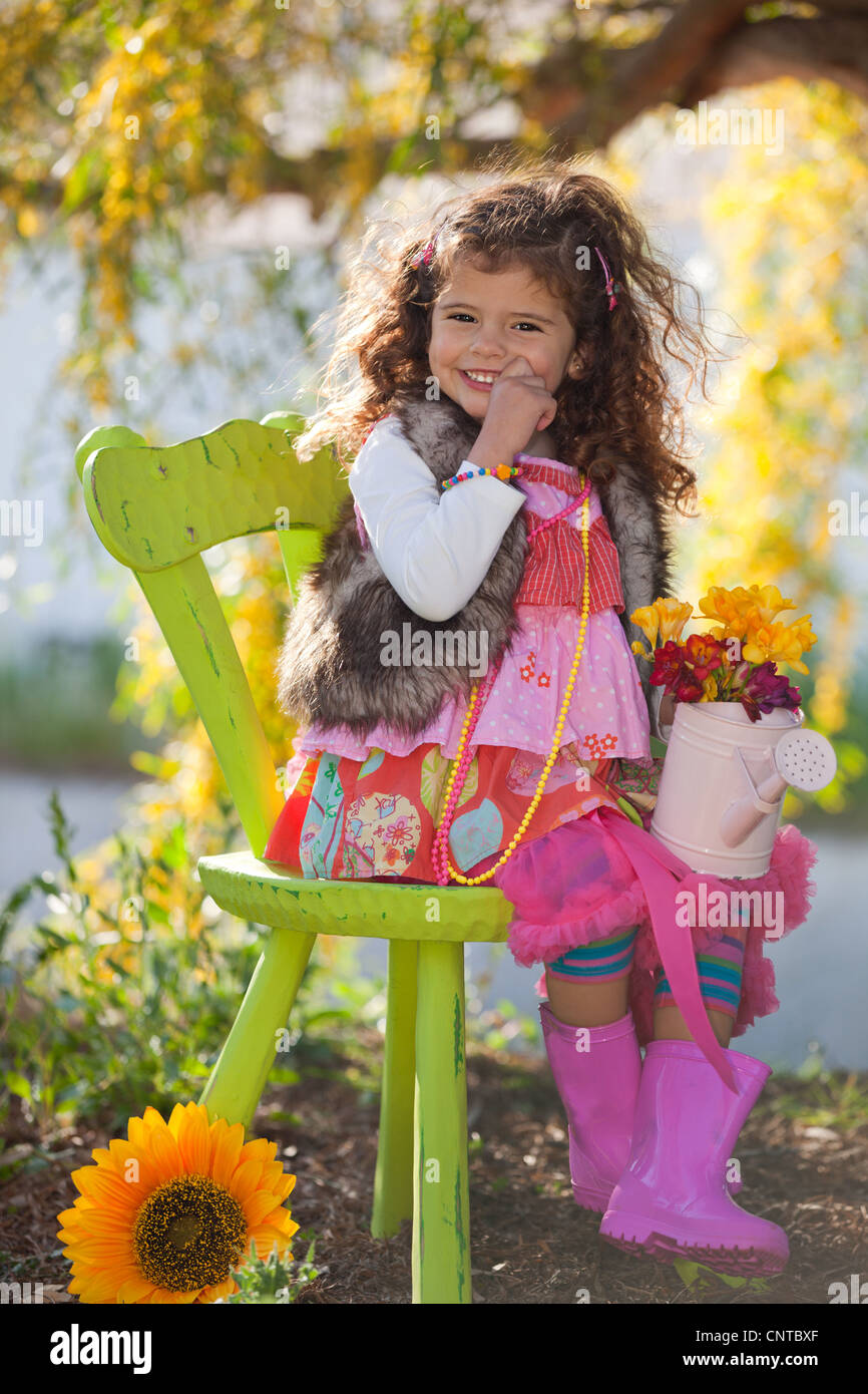 happy cute child sitting in chair outdoors in summer nature, - Stock Image