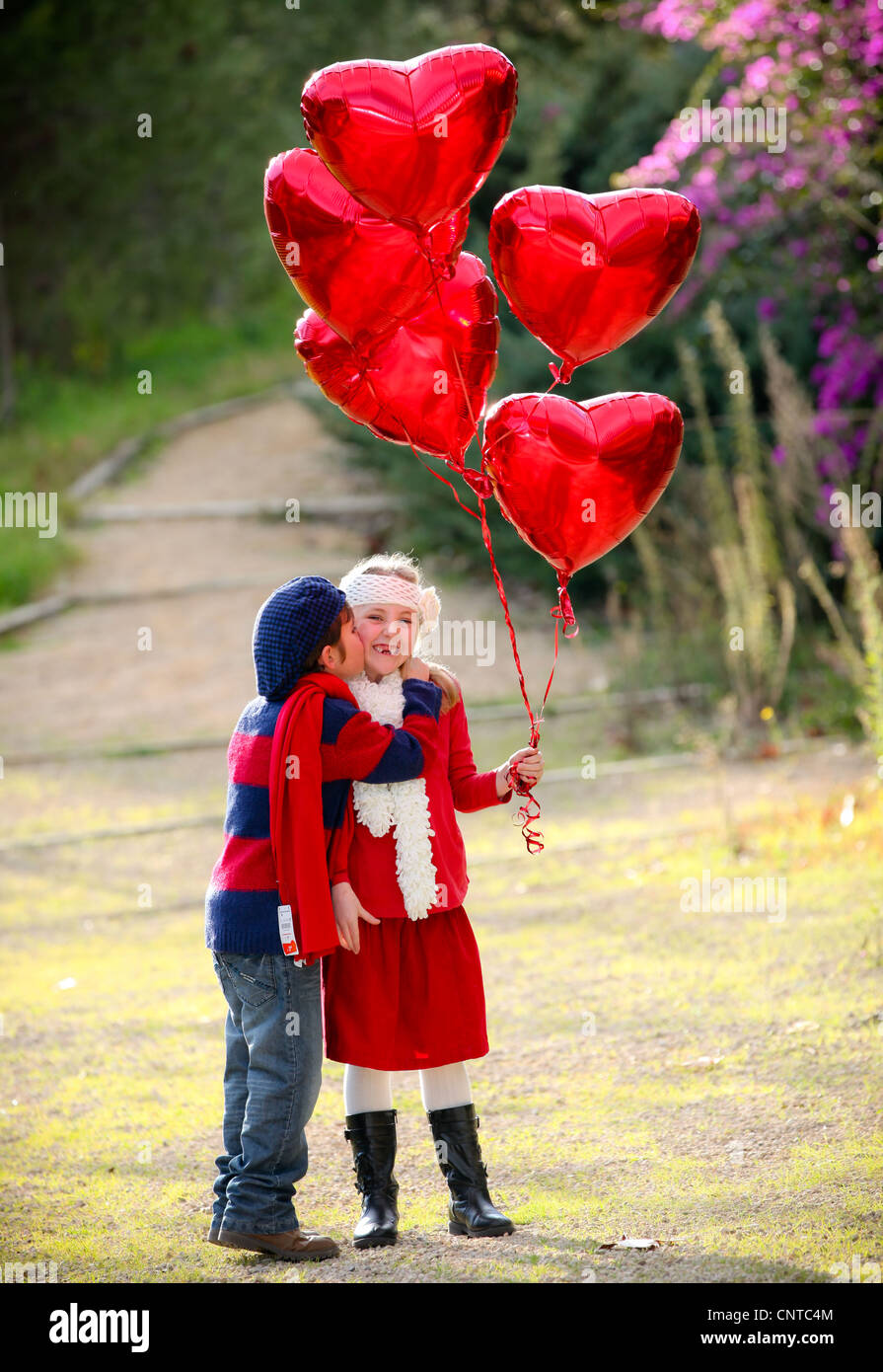 valentines kids with gift of balloons and kiss - Stock Image