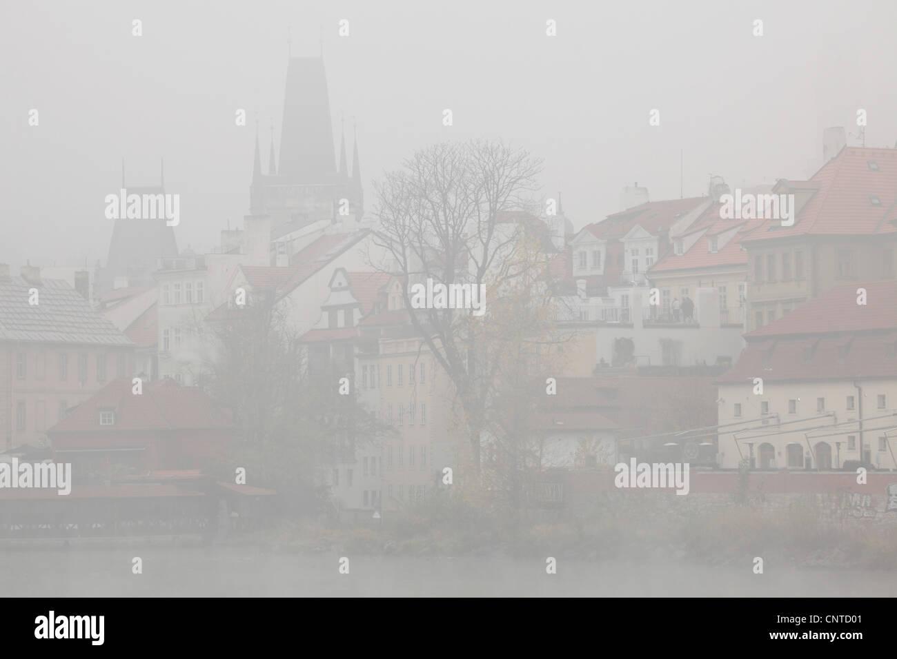 Morning fog over the Vltava River in Prague, Czech Republic. Mala Strana Bridge Towers are seen in the background. - Stock Image