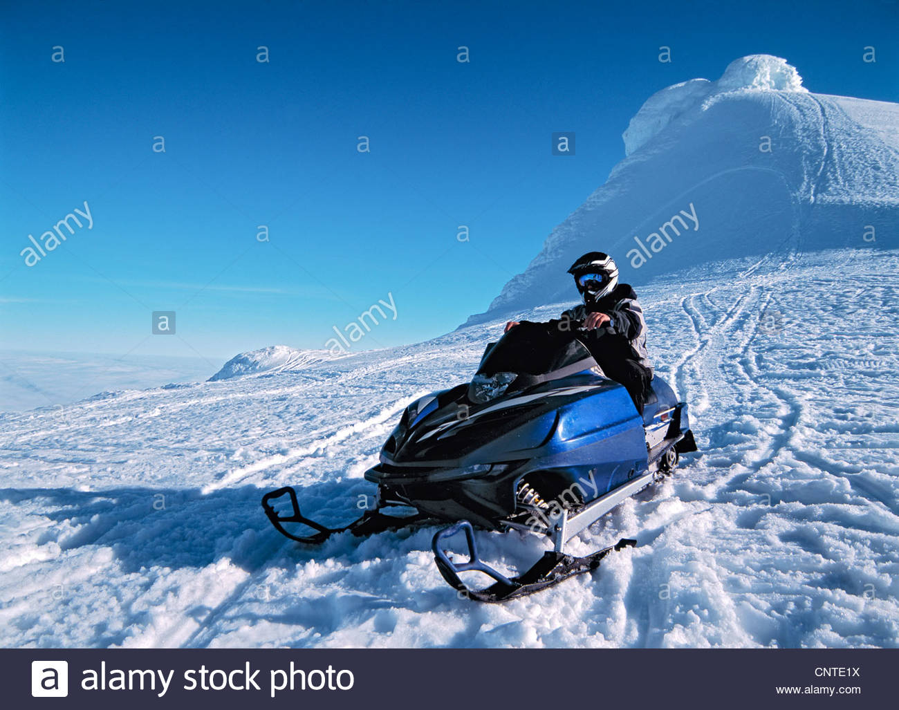Man driving snowmobile over hill - Stock Image