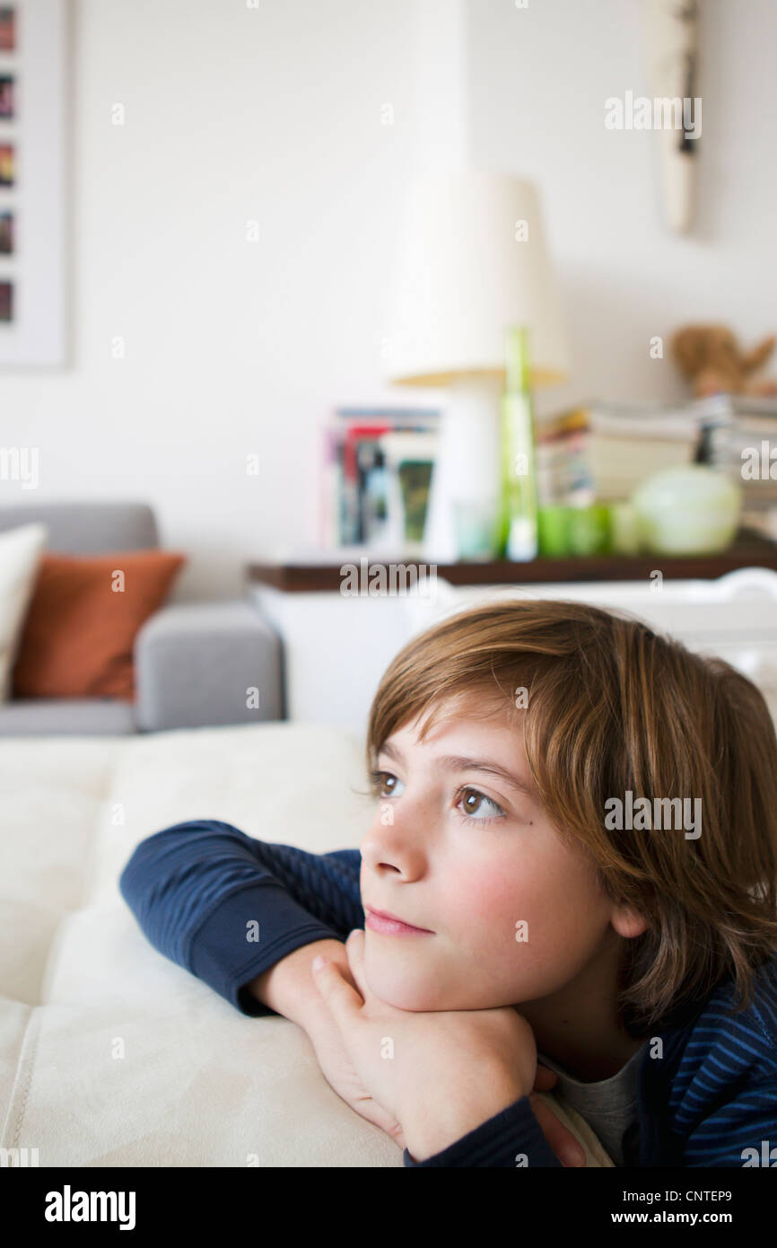 Boy relaxing on sofa in living room Stock Photo