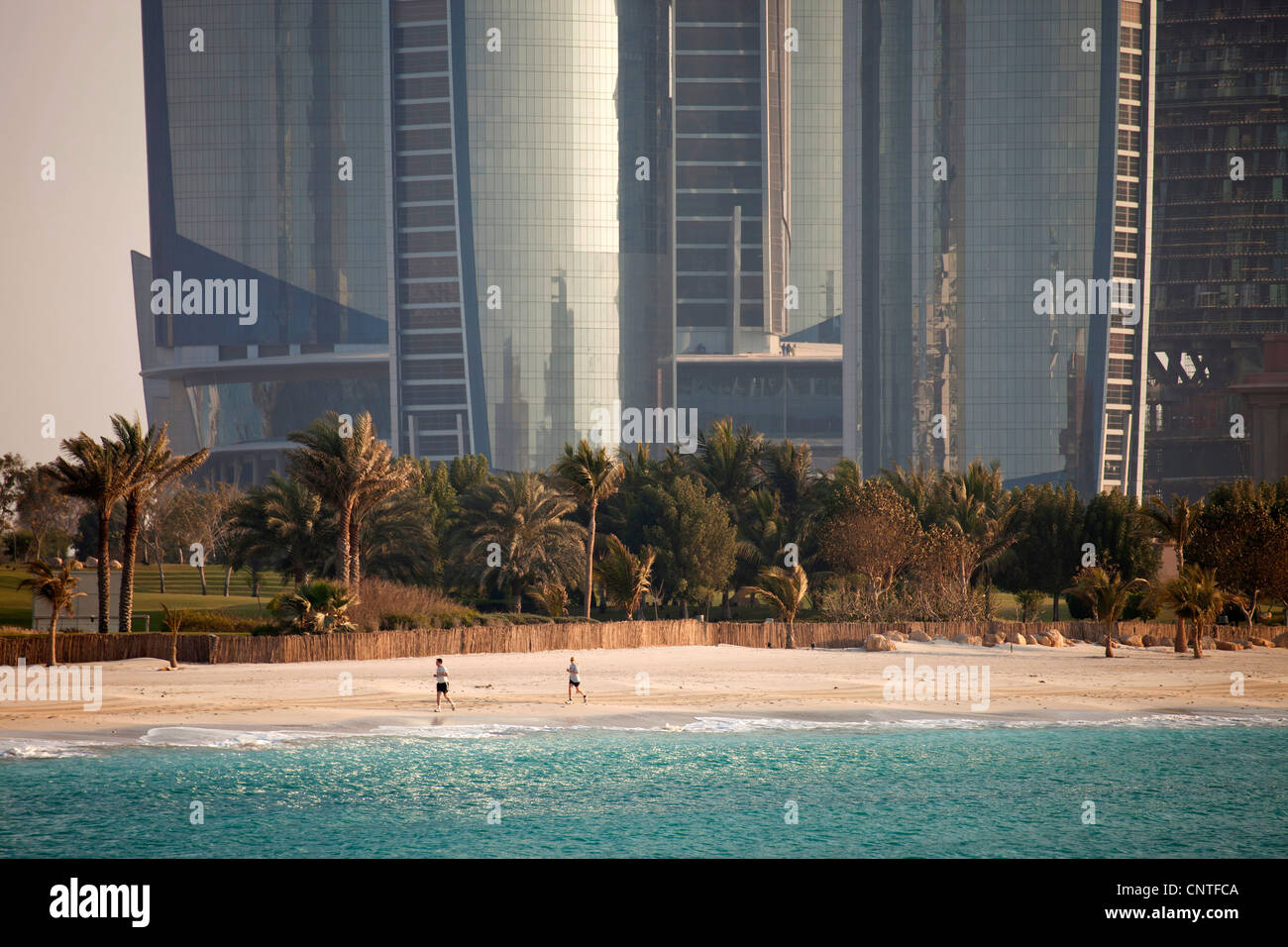 runners at the beach in front of the newly built, modern Skyscrapers Etihad Towers in Abu Dhabi, United Arab Emirates, - Stock Image