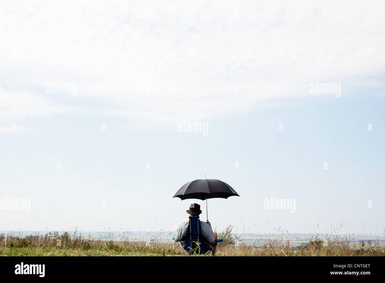 Man sitting under umbrella in field - Stock Image